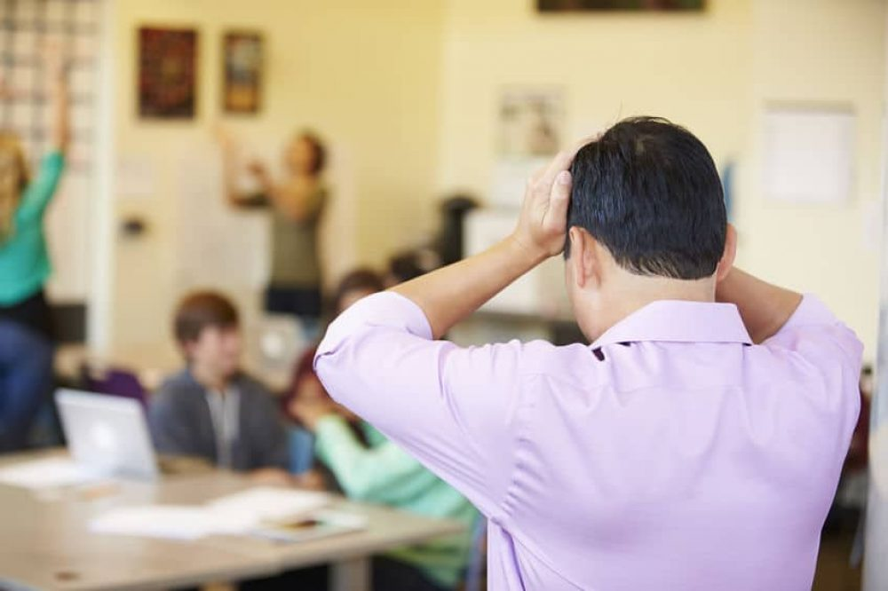 Stressed High School Teacher Trying To Control Class